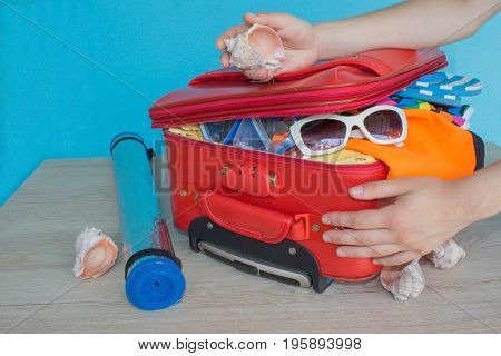 Woman packing stuff into suitcase at home. Travel and vacation concept. Open suitcase with clothes and personal things packed for travelling