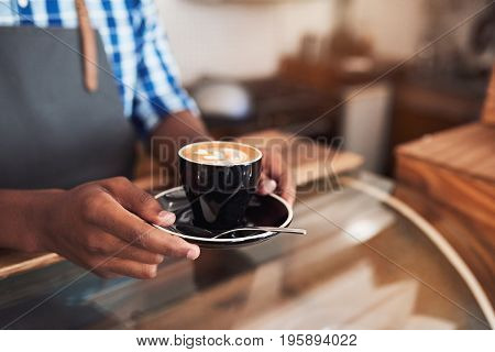 Closeup of a barista standing at the counter of a cafe holding a freshly brewed cup of cappuccino
