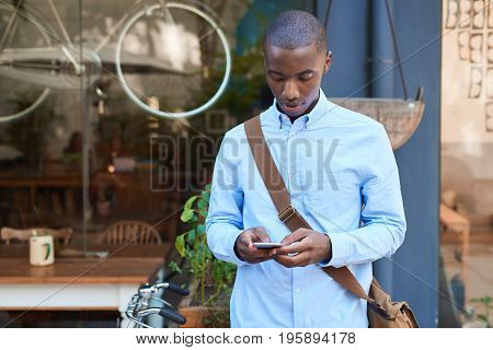 Stylishly dressed young African man standing the street in front of a cafe reading text messages on his cellphone
