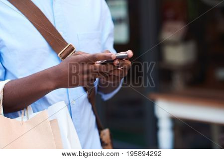 Closeup of a stylish young African man texting on his cellphone and carrying paperbags while out shopping in the city