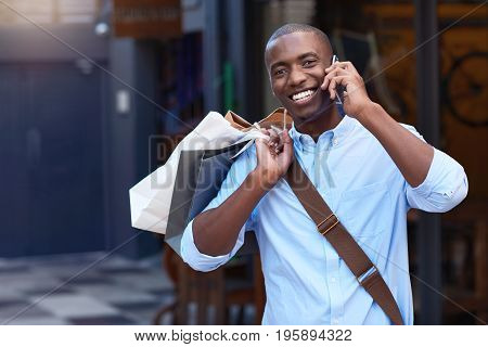 Portrait of a stylish young African man smiling and talking on his cellphone while carrying paperbags while out shopping in the city