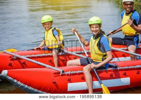Cute girl in helmet and live vest with paddle ready for rafting on the catamaran with her family