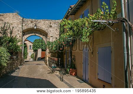 View of traditional Provence houses and arch on a street at sunrise, in Châteauneuf-de-Gadagne. Located in the Vaucluse department, Provence-Alpes-Côte d'Azur region, southeastern France