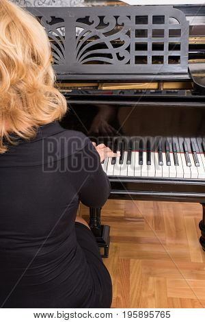 Hands of a classical musician playing on piano.