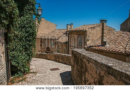 View of typical stone houses with sunny blue sky, in an alley of the historical village of Ménerbes. Located in the Vaucluse department, Provence-Alpes-Côte d'Azur region, southeastern France