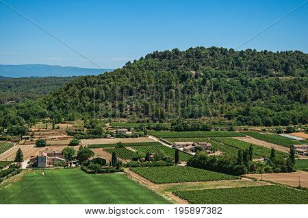 Panoramic view of the fields and hills of Provence near Ménerbes, under sunny blue sky. Located in the Vaucluse department, Provence-Alpes-Côte d'Azur region, southeastern France