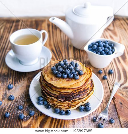 Pancakes healthy breakfast with blueberries, bog whortleberry, cup of green tea, cup of blueberries and teapot on brown wooden background