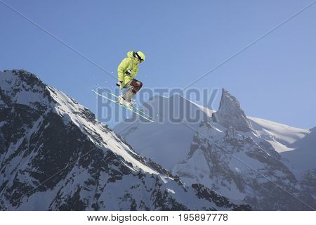 Jumping skier in mountains. Extreme sport, freeride.