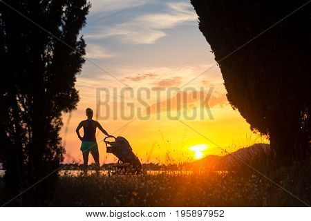 Silhouette of mother with child in stroller enjoying motherhood at sunset landscape. Walking or jogging woman with pram on a beach at sunset. Family relaxing at beautiful inspirational mountains landscape.
