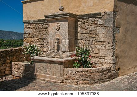 View of stone fountain with flowers and sunny blue sky, at the village of Ménerbes. Located in the Vaucluse department, Provence-Alpes-Côte d'Azur region, southeastern France