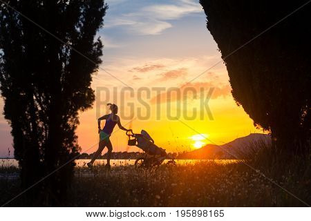 Running mother with child in stroller enjoying motherhood at sunset and mountains landscape. Jogging or power walking woman with pram on a beach at sunset. Beautiful inspirational mountains landscape.