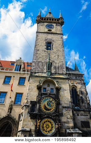 Very rare and old Prague astronomical clock in Old Town Square built at medieval age. The view include whole tower in background are clouds on a blue sky.