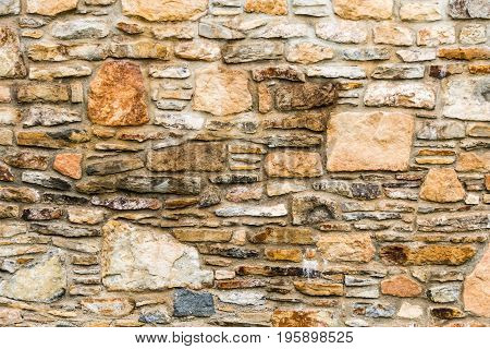 The part of old but nice stone wall. Background texture deep structure irregular pattern.