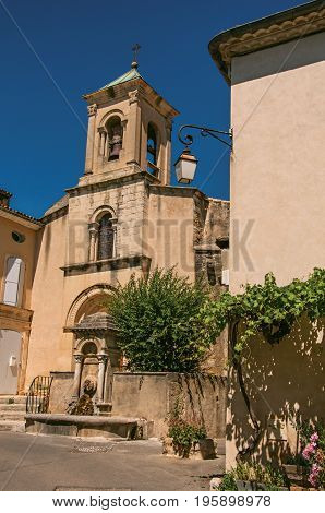 Close-up of church with steeple beside house with flowers, in the historical village of Lourmarin. Located in the Vaucluse department, Provence-Alpes-Côte d'Azur region, southeastern France
