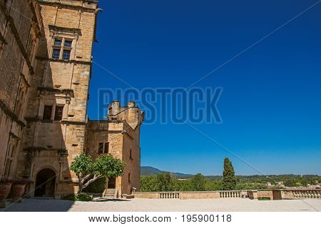 Panoramic of the courtyard and facade of Lourmarin castle with hills in the background, near the village of Lourmarin. In Vaucluse department, Provence-Alpes-Côte d'Azur region, southeastern France