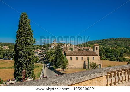 Panoramic view of the village of Lourmarin, its main street and hills in the background. In the Vaucluse department, Provence-Alpes-Côte d'Azur region, southeastern France
