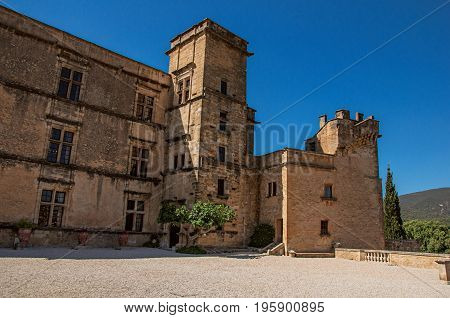 Panoramic of the courtyard and castle facade of Lourmarin with hills in the background, near the village of Lourmarin. In Vaucluse department, Provence-Alpes-Côte d'Azur region, southeastern France