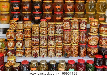 Many glass jars with jam honey and nuts