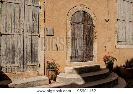 View of colorful house and door with flowers and steps, on a street of the historical village of Lourmarin. Located in the Vaucluse department, Provence-Alpes-Côte d'Azur region, southeastern France