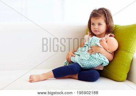 Adorable Little Baby Girl Lulling Doll On Hands