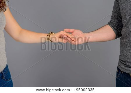 Close up look of the holding hands of a nice young couple