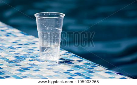 A plastic glass with soda near the pool .