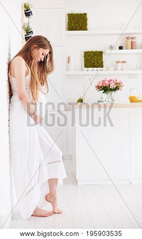 Beautiful Young Pregnant Woman In Frilly Summer Dress At Home