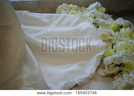 White wedding gown and roses Hem of a white wedding dress with white and yellow roses on the floor
