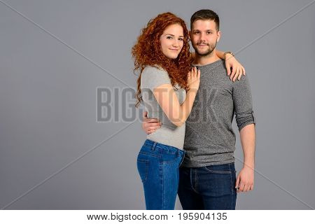A beautiful young couple hugging and holding each other in the studio