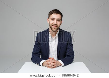 Business Concept - Portrait handsome happy handsome business man in suit smiling and siting in work office. White Background.