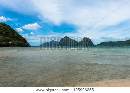 Tropical paradise of El nido at the beach of Las Cabanas with rocks, trees and clean water during sunny day.