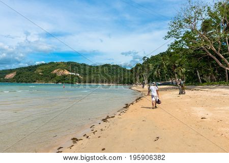 EL NIDO PALAWAN PHILIPPINES - JANUARY 18 2017: People walking at Las Cabanas Beach during a sunny day.