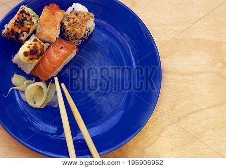 Various sushi rolls and sticks on a blue platter on a wooden background