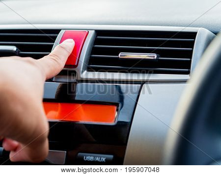 Close up man hand push emergency light button in car.