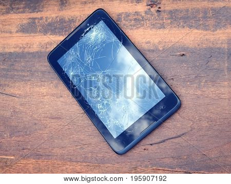 Electronic tablet with broken touch screen in black case on brown wooden background side view closeup