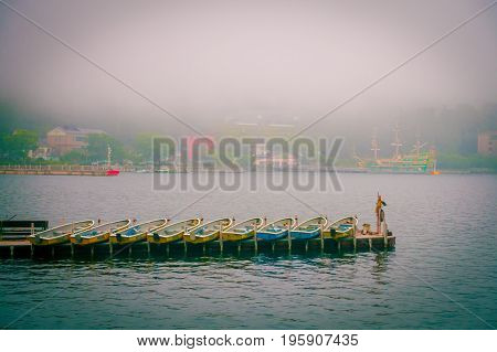 HAKONE, JAPAN - JULY 02, 2017: Fishing boats and red Torii gate of Hakone shrine on lake Ashi on foggy day.