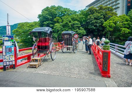 HAKONE, JAPAN - JULY 02, 2017: Unidentifies people over a red bridge at the river at Odawara, transition point to Hakone.