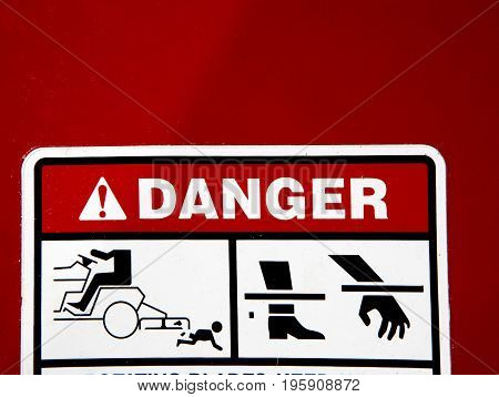Danger: Rotating blades-keep away sign on red tractor