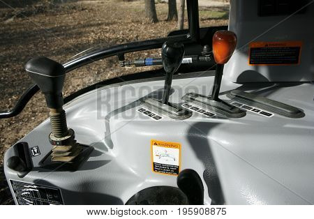 Modern tractor: front loader control joystick, rear attachments controls