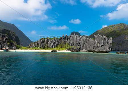 EL NIDO, PALAWAN, PHILIPPINES - JANUARY 19, 2017: Wide angle picture of beach in El Nido's bay with sharp rocks and tropical vegetation.