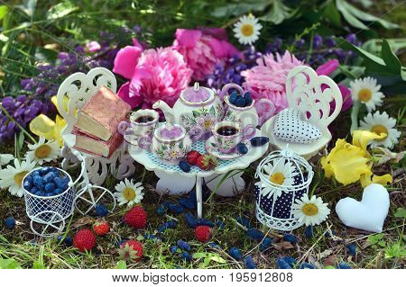 Toy tea service, small furniture, berries and flowers on the grass. Mad tea party concept. Beautiful greeting card with summer flowers and vintage objects. Fairies in the garden