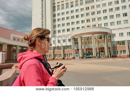 Young female tourist with camera photographing in city center