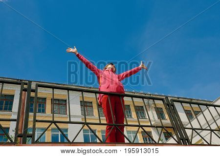 Happy carefree woman with raised hands in city center