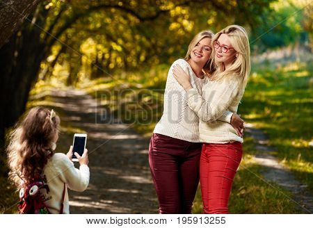 Little girl photographing her elder sisters on smartphone in park