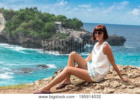 Freedom young caucasian woman sitting and posing on mountain peak rock, cliff. Beautiful blue ocean on the background. Tropical island Nusa Lembongan, Bali, Indonesia, Asia.