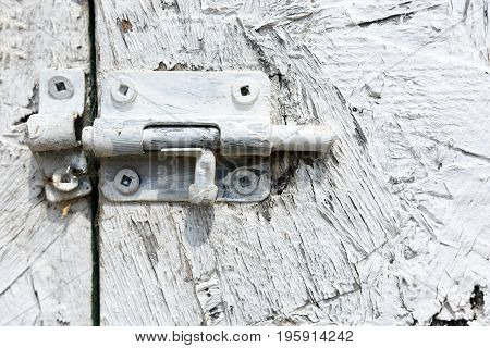 A close up image of an old door latch on a white door.
