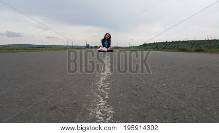 Little girl strolling tired and decided to sit in the middle of the road