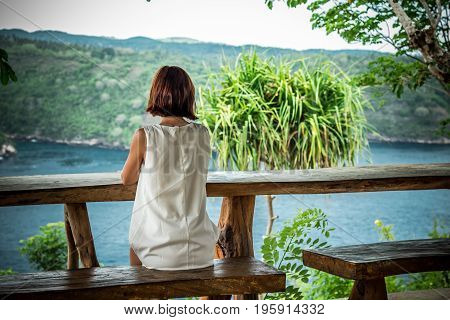 Slim pretty young caucasian women sitting in cafe on the cliff. Tropical island Nusa Lembongan, Indonesia, Asia, sunshine, vacation. Green and blue.