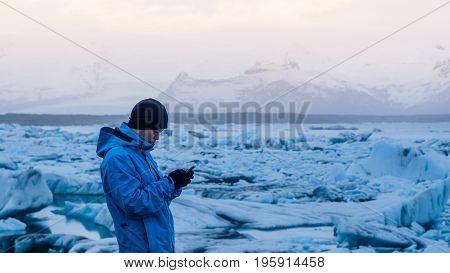 Asian Man Using Smart Phone At Jokulsarlon, Glacier Lagoon Iceland.  World Travel Destination