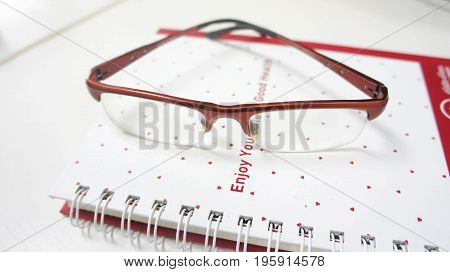 Red glasses are on the note book. Suitable for business purposes.